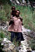 Villager from Dani tribe carrying small child. Papua, Indonesia.