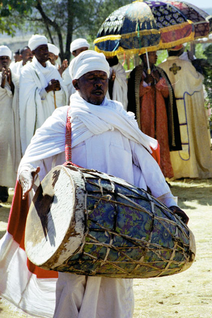 Drumming priest at procession during Timkat. Lalibela. North,  Ethiopia.