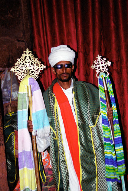 Stone church at Lalibela. Priest shows holy crosses. North,  Ethiopia.