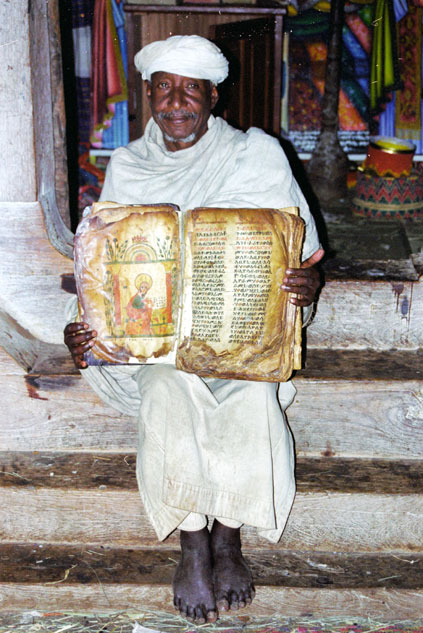 Priest shows old Bible made from goat skin. North,  Ethiopia.