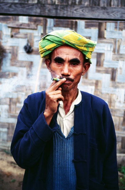Local man (from hill tribe) is smoking traditional burma cigar called cheroot. Area around Kalaw village. Myanmar (Burma).