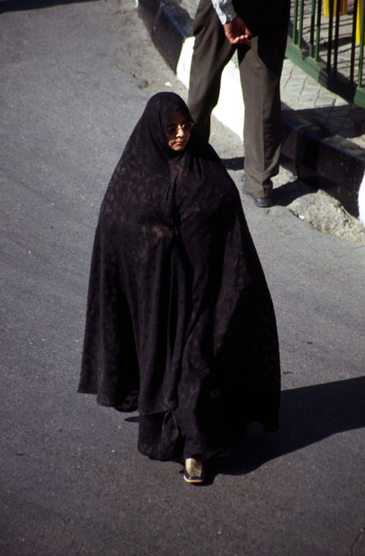Traditional color of woman dress is black in Iran. Woman is dressed in black chador. Mashhad. Iran.