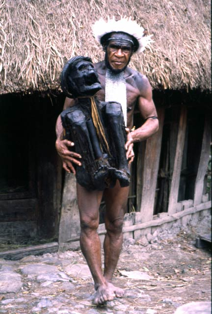 Villager from Dani tribe with 300 years old mummy. Jiwika village. Papua,  Indonesia.