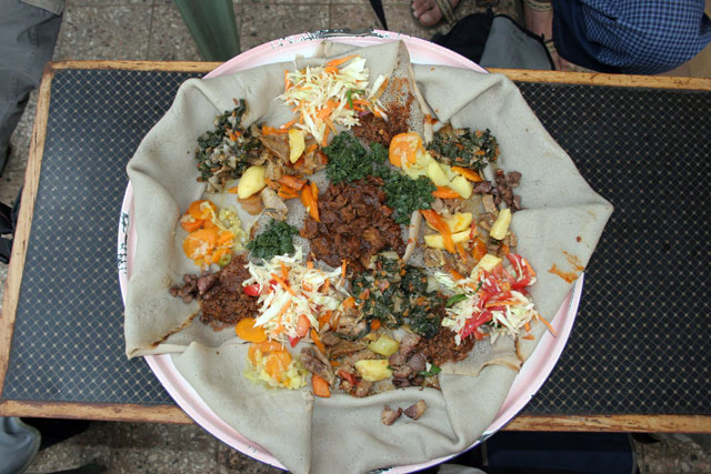 Traditional and common food - injara. Sour pankake served with variety of meet and vegertable. South,  Ethiopia.