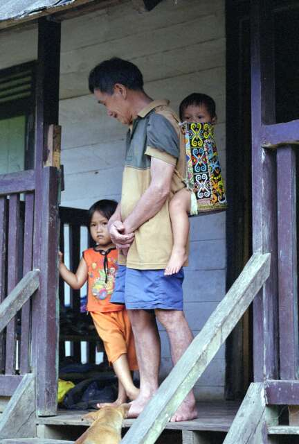 Dayak man is carrying baby in Sungai Barang village. Kalimantan,  Indonesia.