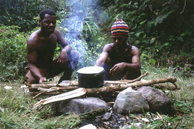 Guides are cooking lunch during trekking. Papua,  Indonesia.