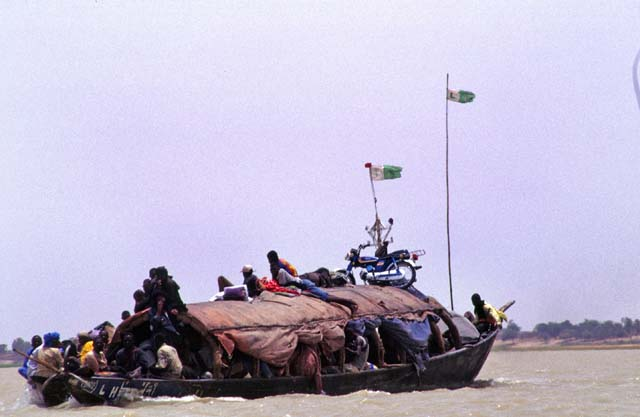 Life at Niger river. Large pinnase boat is carrying passangers and goods on the river. Mali.