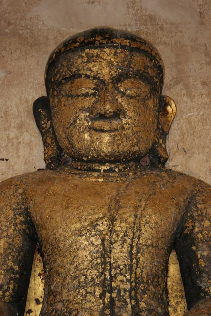 Buddha statues are often decorated by golden papers. Bagan. Myanmar (Burma).