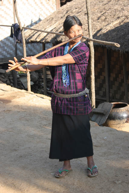 Woman from Dai Chin tribe playing at nose flute, Mindat village, Chin State. Myanmar (Burma).