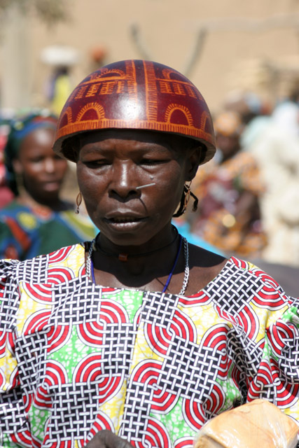 Woman at Tourou village at Mandara Mountains. Local fashion is red wooden calabashes on women' heads. They look rather like army helmets and which indicate things like their marital status. Cameroon.