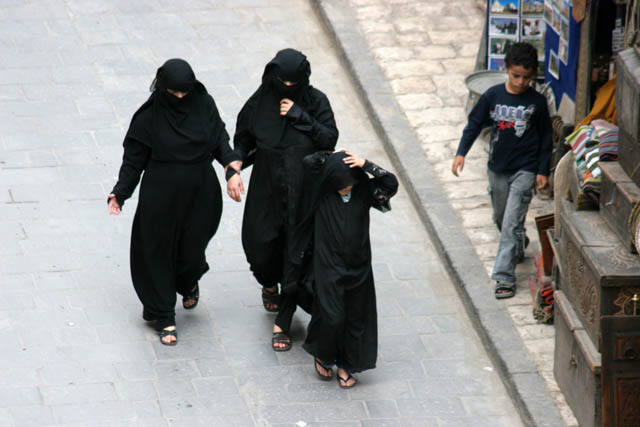 Women at traditional black clothes at street at old quarter of Sana capitol. Yemen.